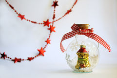 Cute christmas bear statuette in a glass bottle on white backgro. Cute yellow christmas bear statuette in a glass bottle on white background with red garland Royalty Free Stock Images