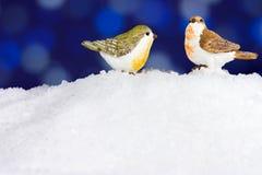 Cute Christmas birds. Christmas winter robin figurine on snow Stock Photos