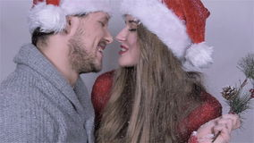 Cute Christmas couple blowing snow over white background.
