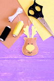 Cute Christmas deer made of felt. Yellow and brown felt pieces, thread, needle, scissors on lilac wooden background Stock Photography