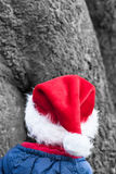 Cute Christmas Elf with red pointed Hat in the Forest. Rear of a little boy christmas imp with red pointed hat in front of a strong tree Stock Image