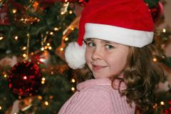 Cute Christmas girl. Little girl wearing a Santa hat in front of a Christmas tree Royalty Free Stock Photos