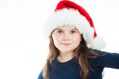 Cute Christmas Girl. Portrait of a little cute girl wearing a Christmas Hat, looking straight into the camera. Isolated on white background Royalty Free Stock Image