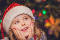 Cute Christmas girl portrait. Cute Christmas girl with the Christmas tree lights bokeh in the background Stock Image