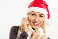 Cute Christmas Girl. A young pretty blonde girl with Santa's hat on her head, smiling looks into the camera and tucking it into her scarf Royalty Free Stock Photography