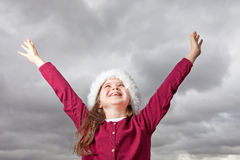 Cute Christmas girl. Cute young girl standing outside, wearing a red Santa hat, her arms stretched out up in the air Stock Photography