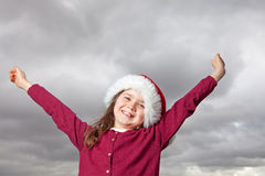 Cute Christmas girl. Cute young girl standing outside, wearing a red Santa hat, her arms stretched out up in the air Royalty Free Stock Photo