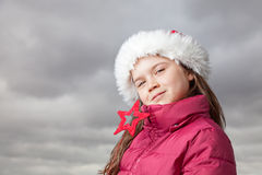 Cute Christmas girl. Cute young girl standing outside, wearing a red Santa hat,looking into the camera Stock Photos