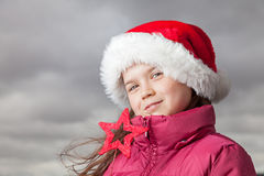 Cute Christmas girl. Cute young girl standing outside, wearing a red Santa hat,looking into the camera Stock Images