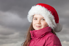 Cute Christmas girl. Cute young girl standing outside, wearing a red Santa hat,looking into the camera Stock Image
