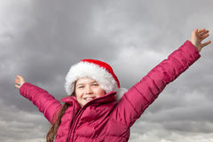 Cute Christmas girl. Cute young girl standing outside, wearing a red Santa hat,looking into the camera, her arms stretched out up in the air Stock Image