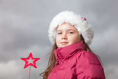 Cute Christmas girl. Cute young girl standing outside, wearing a red Santa hat,looking into the camera, holding a red Christmas star in her hands Royalty Free Stock Images