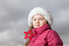 Cute Christmas girl. Cute young girl standing outside, wearing a red Santa hat,looking into the camera, holding a red Christmas star in her hands Stock Photography