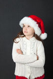 Cute Christmas Girl. Young girl wearing a white wooly sweater and a red Santa hat Royalty Free Stock Photo