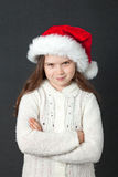 Cute Christmas Girl. Young girl wearing a white wooly sweater and a red Santa hat Royalty Free Stock Images