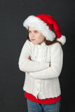 Cute Christmas Girl. Young girl wearing a white wooly sweater and a red Santa hat Stock Photos