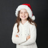 Cute Christmas Girl. Young girl wearing a white wooly sweater and a red Santa hat Royalty Free Stock Photos