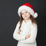 Cute Christmas Girl. Young girl wearing a white wooly sweater and a red Santa hat Stock Images