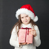 Cute Christmas Girl. Young girl wearing a white wooly sweater and a red Santa hat Stock Photo
