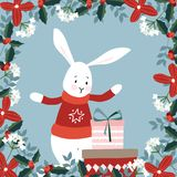 Cute Christmas greeting card, invitation with hand drawn bunny and gift boxes. Floral frame made of holly berries Stock Photography