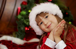 Cute Christmas little girl in Santa hat Stock Photos