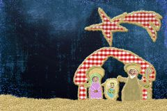 Cute Christmas Nativity Scene  greeting card. Nativity Scene made with cheerful cuts of fabrics and golden glitter on blu background with copy space Royalty Free Stock Image
