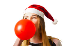 Cute christmas party planner. Cute portrait on the head of adorable blond girl in santa hat blowing up a red balloon in preparation for celebrations. Christmas Royalty Free Stock Images