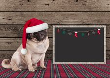 Cute Christmas  pug puppy dog with santa hat and blackboard on wooden background. And plaid pattern ground Stock Photos
