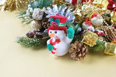 Cute Christmas snowman nestled in decorations. With gift boxes and pine tree branches Stock Images