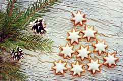 Cute christmas tree concept with cinnamon star cookies. Vintage greeting card with cones on white wooden cracked background Royalty Free Stock Photography