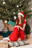 Cute Christmas Woman Wearing Santa Hat Pulls A Gift royalty free stock photo