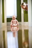 Cute chubby baby on floor laughing at mom. Cute seven month old chubby baby wearing diaper sitting on floor laughing at mother royalty free stock images