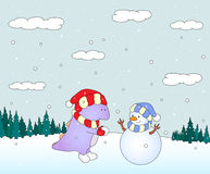 Cute chubby dragon sculpts snowman in a snowy forest. Christmas Royalty Free Stock Images