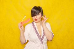 Cute chubby girl in a pink robe stands with a comb and toothbrush on a yellow background in the Studio. Alone royalty free stock photos