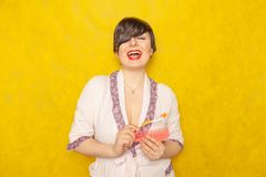 Cute chubby girl in a pink robe stands with a comb and toothbrush on a yellow background in the Studio. Alone royalty free stock photography