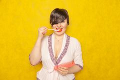 Cute chubby girl in a pink robe stands with a comb and toothbrush on a yellow background in the Studio. Alone stock image