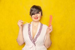 Cute chubby girl in a pink robe stands with a comb and toothbrush on a yellow background in the Studio stock photo