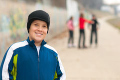 Cute chubby teenage boy having fun with friends. On the street on cloudy autumn day stock photos