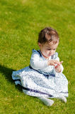 Cute chubby toddler looking at dandelion seeds curiously exploring nature outdoors in the park Stock Photos
