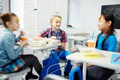Play at lunch. Cute classmates sitting in classroom and playing name game at lunch break Royalty Free Stock Image