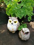 Cute clay owls. Two cute clay owls standing on flagstone with fern leaf background Stock Photos