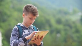 Cute clever boy with tablet, tablet in hands outdoors. Education in elementary school with tablet. New technology. Education in elementary school with tablet stock video