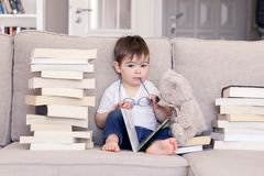 Cute clever funny little baby boy with thoughtful serious face expression holding glasses in hands reading book sitting on sofa wi. Th teddy bear toy and piles stock photography
