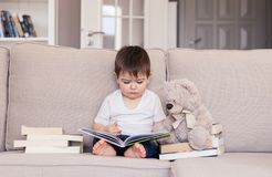 Cute clever little baby boy keen about reading book sitting on sofa with teddy bear toy and pile of books at home. Child education and development concept royalty free stock photography