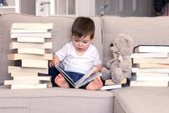 Cute clever little baby boy keen about reading book sitting on sofa with teddy bear toy and piles of books stock photography