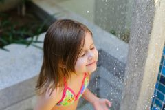 Cute close portrait drops of water fall on little girl in swimsu Stock Photos