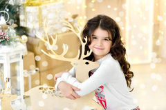 Cute close up portraite of curly girl with gold Christmas garlands magic lights and tree decorations hugs toy deer. Holiday background, new year Stock Photography