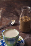 Cute coffee cup and raw sugar in glass bottle Stock Images