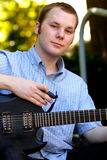Cute College Boy with Guitar. A typical american college boy sitting on some stairs playing a guitar. Short hair, shallow depth of field, selective focus Royalty Free Stock Photo