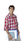 Cute college guy. Cute indian college guy holding books and notes with carefree expression Royalty Free Stock Images